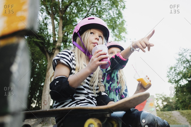 Girl pointing and showing to friend while having juice at skateboard park
