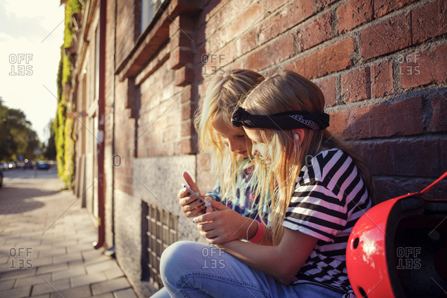 Girls using mobile phone while sitting against brick wall on sunny day