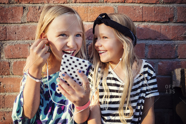 Happy girls listening music through smart phone while sitting against brick wall