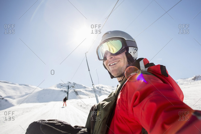Smiling man in ski-wear on snow covered field against clear sky