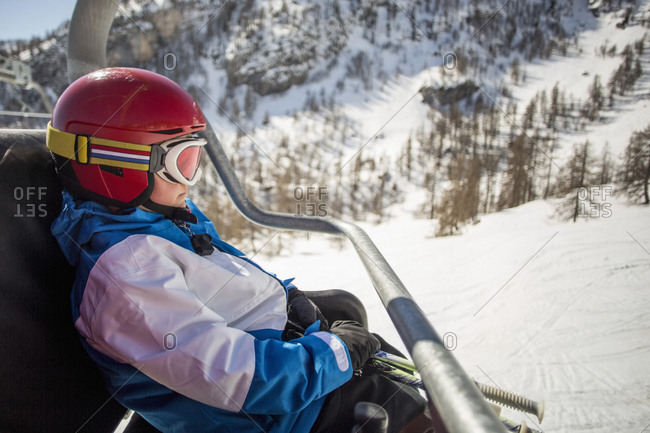 Side view of boy traveling in ski lift