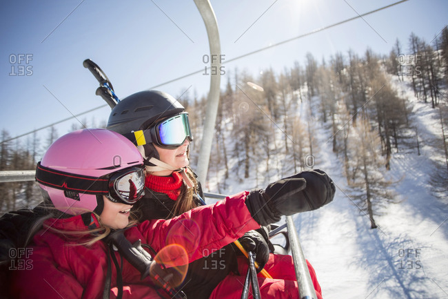 Mother and daughter enjoying while traveling in ski lift