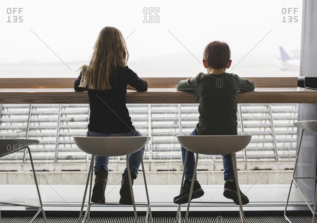 Rear view of siblings sitting on seats by window in restaurant