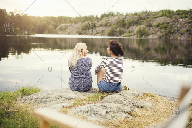 Rear view of female friends talking while sitting at lakeshore