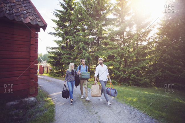 Full length of friends with luggage walking on footpath amidst cottage and trees
