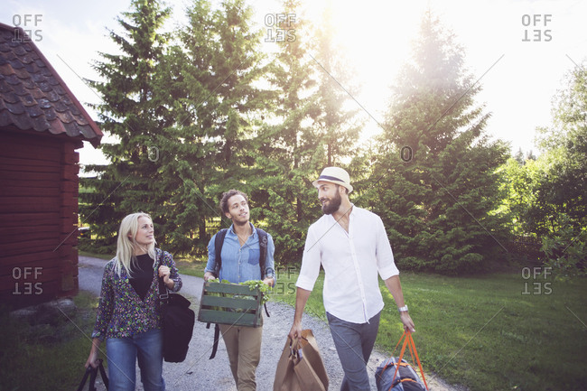 Friends with luggage talking while walking on footpath against trees