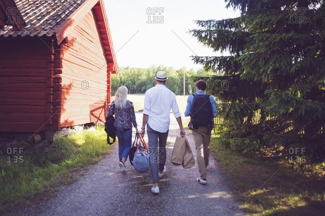Rear view of friends with luggage walking on footpath amidst cottages and trees
