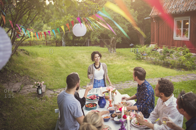 High angle view of woman talking to friends at table in garden party