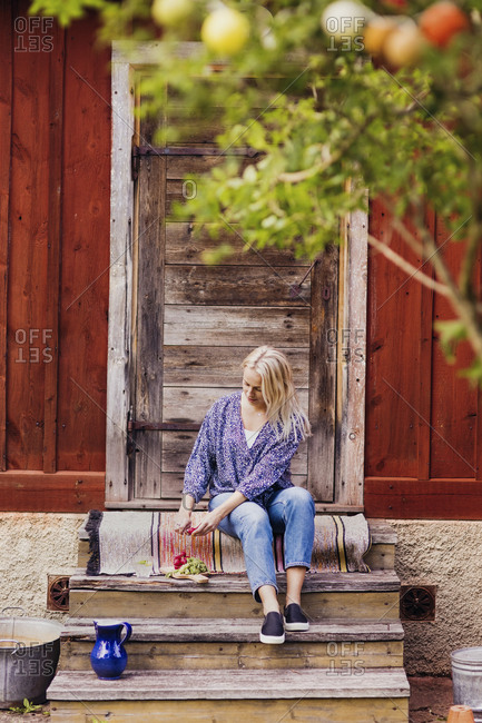 Full length of woman cutting radishes while sitting on steps outside wooden cottage