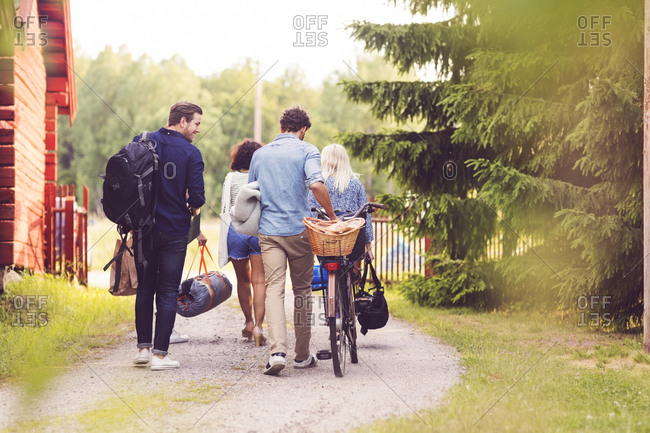 Rear view of friends walking with bicycle and luggage on footpath by trees
