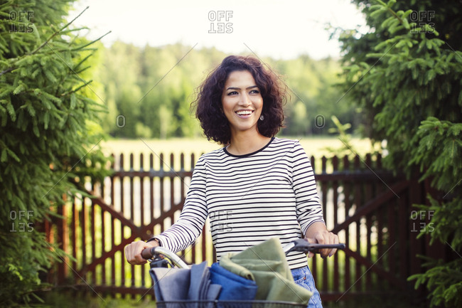 Happy woman with bicycle standing against fence amidst plant