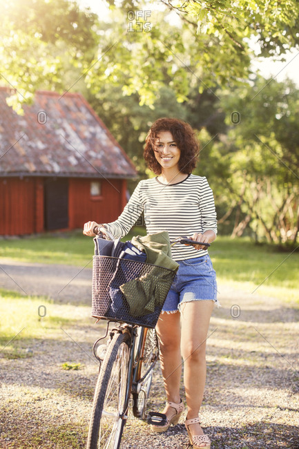 Portrait of smiling woman with bicycle standing at backyard