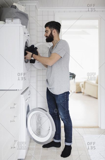 Side view of man loading clothes in washing machine at home