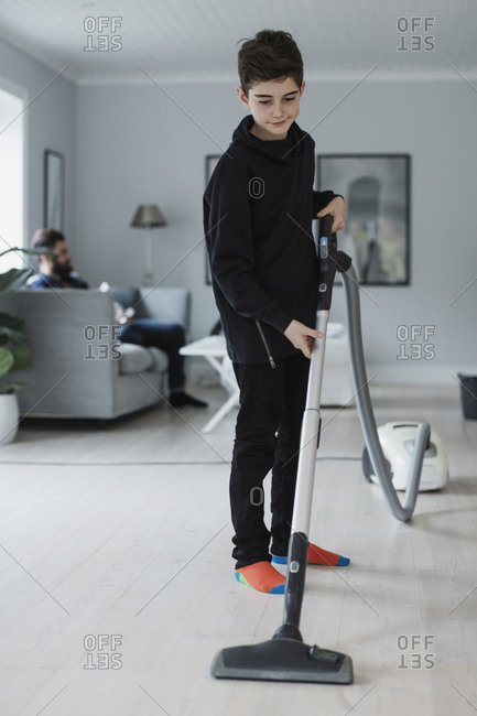 Boy cleaning floor with vacuum cleaner at home