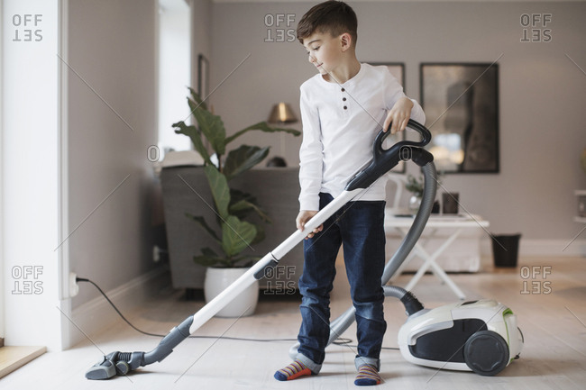 Boy using vacuum cleaner in living room at home