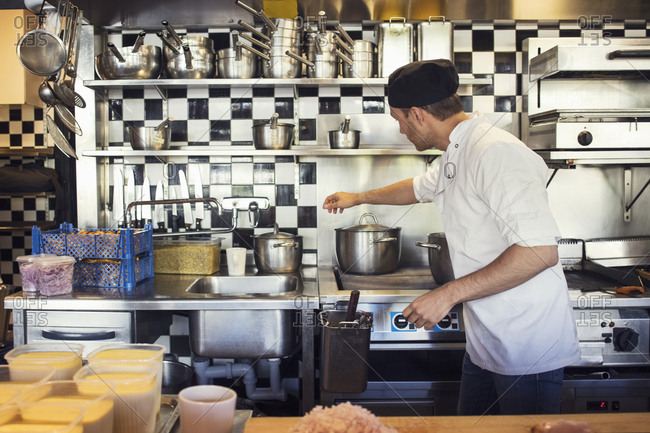 Male chef cooking in kitchen at restaurant