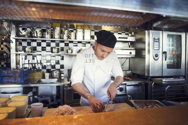 Male chef chopping onion cutting board in restaurant kitchen