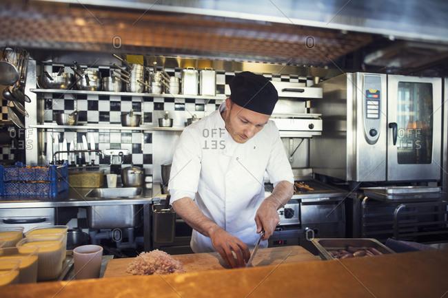 Male chef chopping onion cutting board in restaurant kitchen