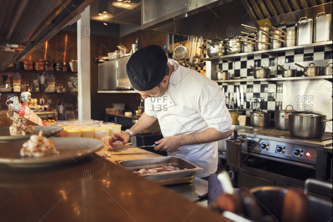 Chef chopping onion cutting board in kitchen at restaurant