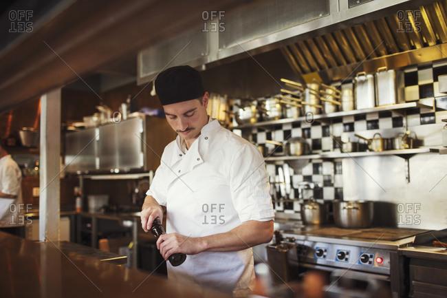 Waiter holding pepper mill at restaurant