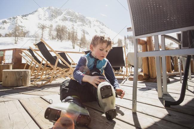 Boy wearing ski boots by seat on floorboard