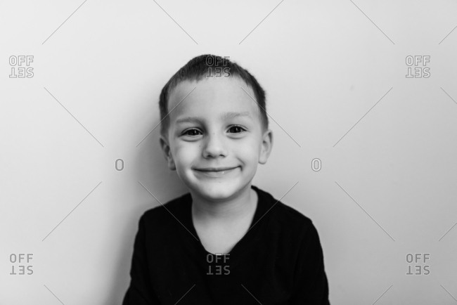 Boy wearing a black t-shirt smiling at the camera