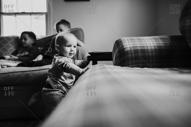 Toddler boy standing near a couch in a living room with his brothers