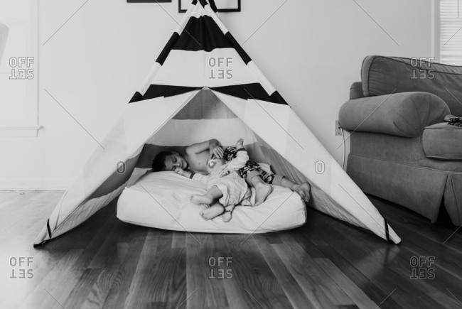 Two brothers lying on a cushion inside a tent indoors