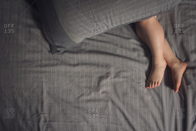 Bare feet of a toddler lying under a pillow in bed