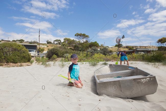 Two boys digging in sand by a beached rowboat