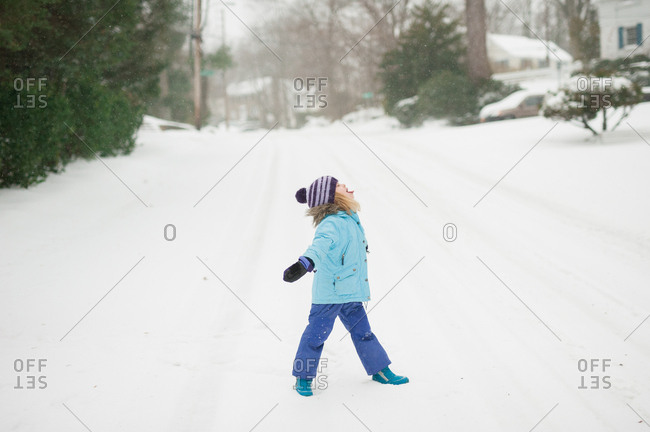 Girl catching snowflakes on tongue while standing on a snow covered road in neighborhood