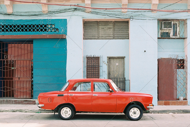 Havana, Cuba - March 20, 2017: Vintage red car parked on street in front of residential buildings