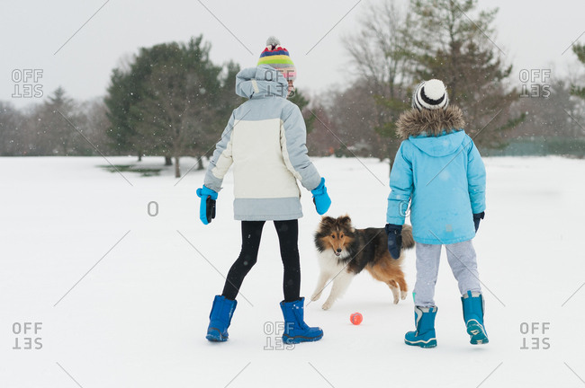 Two children playing ball with their pet dog in the snow
