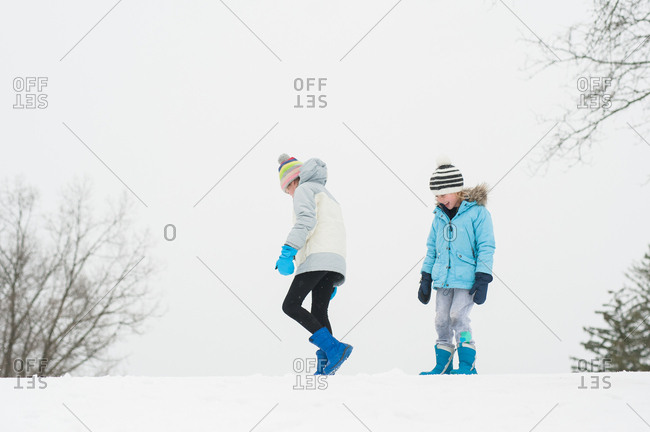 Two children walking outside in the snow