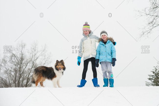 Two children standing together outside in the snow with their pet dog