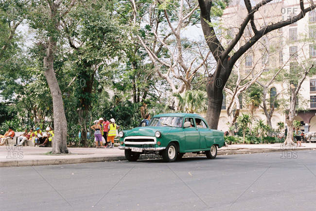 Havana, Cuba - March 20, 2017: Vintage green car parked on street in front of city park