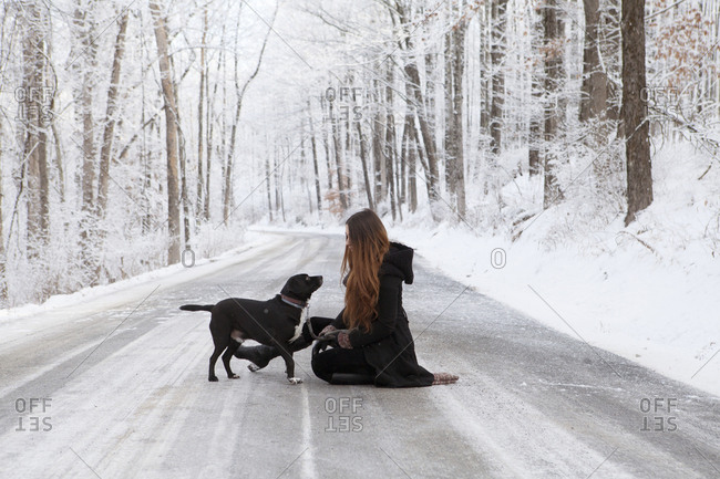 Side view of woman with dog on road during winter