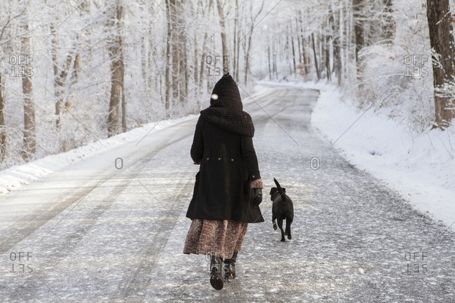 Rear view of woman walking with dog on road during winter