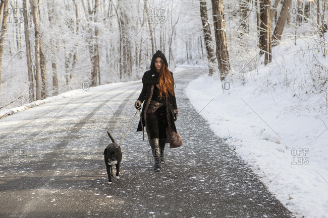 Portrait of young woman walking with dog on road during winter