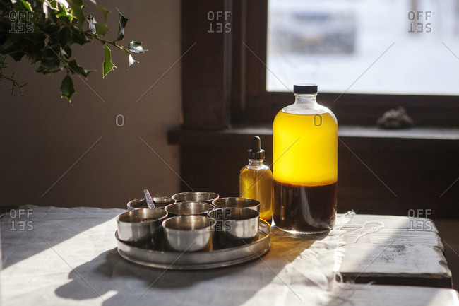 Containers by oil in bottles on table