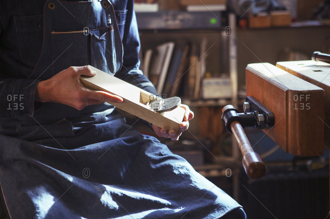 Midsection of carpenter holding wood plane while sitting at workshop
