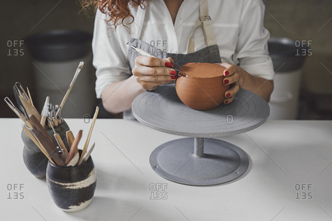 Midsection of female potter molding shape to clay with work tool at table