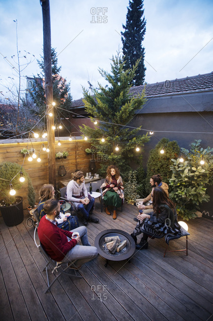 High angle view of friends enjoying drinks while sitting in backyard at dusk
