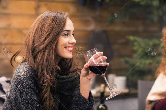 Happy woman enjoying wine while sitting in backyard at night