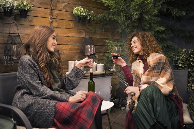Female friends enjoying wine in backyard at night