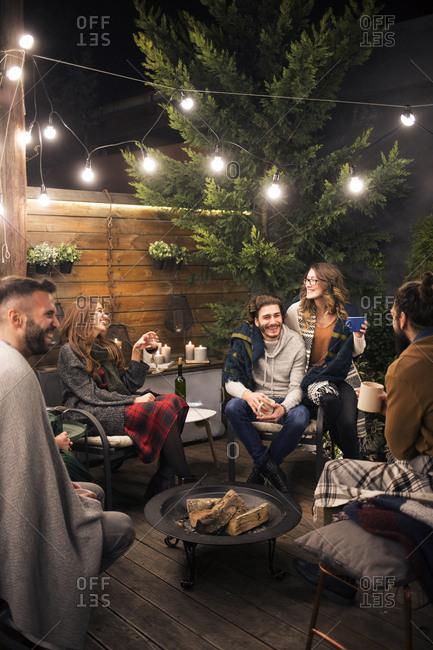 Friends enjoying party in backyard at night