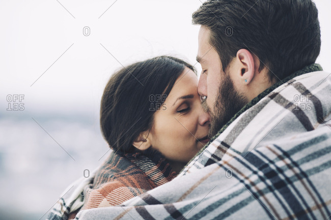 Close-up of romantic couple wrapped in scarf