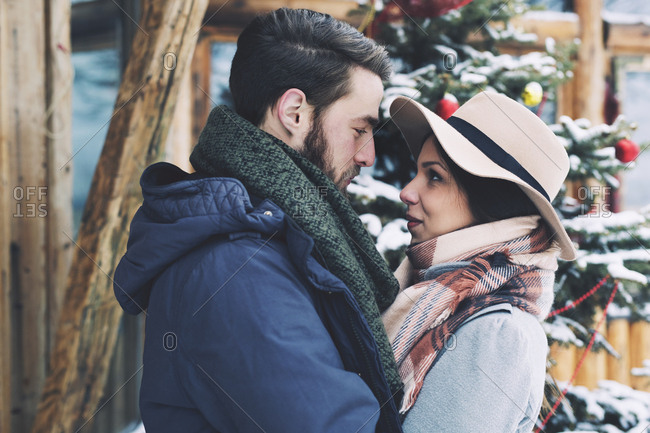 Romantic couple looking at each other while standing by Christmas tree
