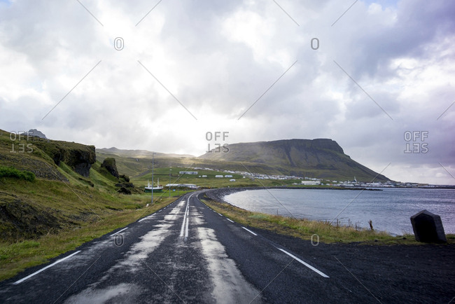 Scenic view of empty road by sea against cloudy sky