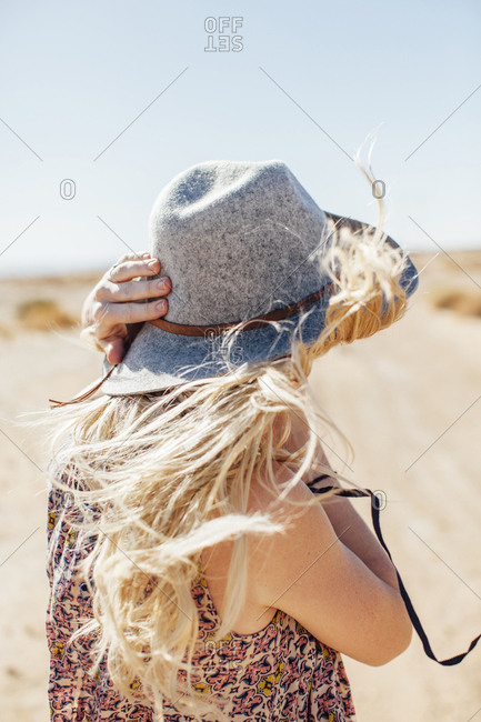 Woman in sun hat standing against at desert against clear sky during sunny day